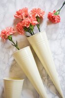 Salmon-pink carnations in conical metal vases on marble surface