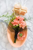 Bouquet of carnations in ceramic bowl and sponge fingers tied with string on marble surface