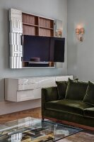 Glass coffee table, sofa and open wall-mounted TV cabinet above white floating sideboard