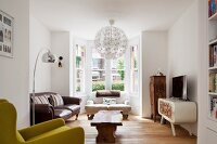 Bay window, spherical pendant lamp, wooden coffee table and antique sofas in eclectic interior