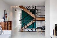 View from living space into open-plan stairwell with black metal balustrades and elegant wooden staircase