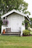 White wooden summerhouse with small veranda and hanging baskets