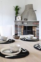 Place settings with black place mats on wooden table in front of brick fireplace