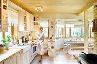 Pale wooden ceiling, woman wearing apron in front of kitchen counter and dining area in window bay in open-plan kitchen
