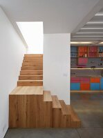 Wooden landing and staircase with view of colourful fitted kitchen to one side
