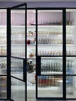 Floor-to-ceiling glass wall with black steel frame and double doors with view of open-fronted shelves in pantry