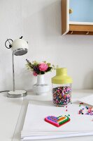 Colourful fusion beads and posy in retro vase on white desk