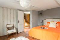 Double bed with orange bed linen in renovated bedroom with view of rustic wooden staircase