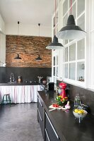 Black kitchen counters in loft apartment with brick wall and polished concrete floor