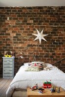 Bed below star-shaped lamp on rustic brick wall in boy's bedroom