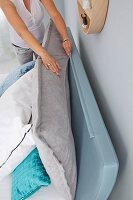 A woman zipping together a headboard cushion with a headboard