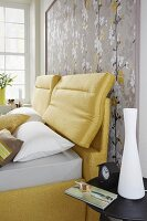 A yellow boxspring bed against framed Japanese-style wallpaper