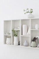 Collection of vases in white-painted, wall-mounted, retro display case