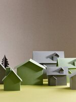 Green and grey cardboard models of houses on yellow surface