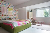 Colourful wallpaper on accent wall and green upholstered bed frame in bright bedroom