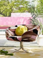 Retro swivel chair with patterned cover and yellow scatter cushion on terrace in front of pool and garden wall painted pink