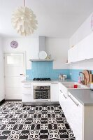 White kitchen cabinets, pale blue wall tiles and black and white cement floor tiles