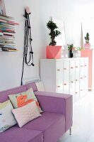 Scatter cushions on lilac couch next to Bonsai tree on top of white retro cabinet