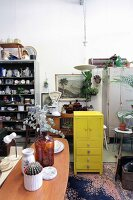 Various flea-market finds and vintage items around yellow-painted wooden chest of drawers