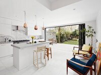 Island counter, retro armchairs and table and open sliding doors leading to garden in white modern kitchen-dining room