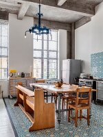 Ornate tiles and eclectic furnishings in open-plan kitchen with tall industrial windows