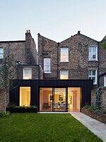 Modern extension with illuminated interior built onto traditional, English brick house seen from garden