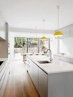 Row of yellow pendant lamps above white island counter in modern kitchen with open terrace doors