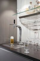 A glass of beer under a tap in a kitchen