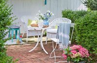 A terrace with white wicker chairs, a folding chair and table in a summery garden