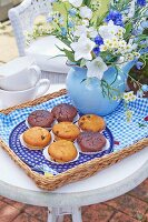 Muffins and a summery bouquet of flowers on a tray with a homemade fabric cloth