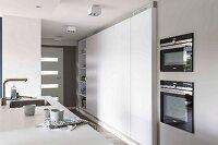 Detail of a kitchen counter opposite a modern, built-in kitchen cupboard in white in an open-plan kitchen