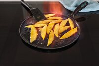 Pans with flambéed mango pieces on an induction stove