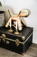 Gold dog figurine and candles on antique miniature trunk with brass latches