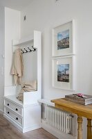 Cushions and coat pegs on white cloakroom cabinet next to framed photos