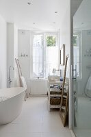 White, free-standing bathtub in bathroom