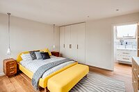 Yellow bed and fitted wardrobes in bedroom with ensuite bathroom