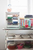 Crockery and small display case on old serving trolley