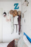 Various items of clothing and hats hung from coat pegs in bedroom