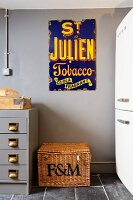 Old enamel advertising sign above wicker trunk