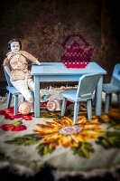 Pale blue dolls' furniture and macabre, antique male china doll on embroidered blanket