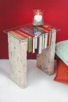 DIY side table made from two rustic boards, drilled books and glass top
