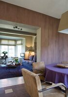 Purple wall and dining area with retro leather chairs in restored period apartment