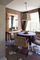 Console table and retro armchairs at round table in dining area