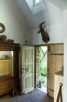Antique wooden doors and hunting trophy in renovated country house