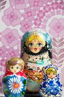 Three Russian dolls in front of pink floral wallpaper
