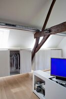 Clothes racks in custom floating wardrobes and blue monitor on foot of white bed in attic bedroom