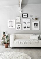 Sofa below gallery of pictures in monochrome living room