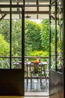 Open door leading to table and chairs in loggia with view of garden