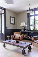 Comfortable vintage leather armchairs and rustic coffee table on castors in traditional living room