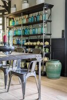 Coloured soda siphons and ceramic vessels on open shelves behind rustic table and chairs